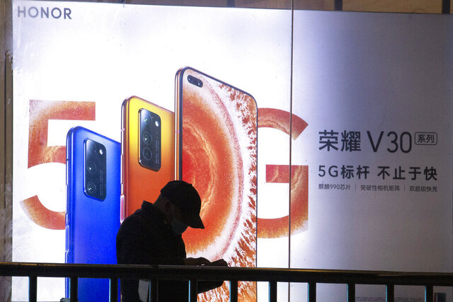 A man stands near an advertisement for Huawei's Honor brand 5G phones in Beijing on Thursday, Feb. 27, 2020. In an announcement Tuesday, Nov. 17, 2020, Chinese tech giant Huawei says it is selling its budget-price Honor smartphone brand in an effort to rescue the struggling business from damaging U.S. sanctions imposed on its parent company. (AP Photo/Ng Han Guan)