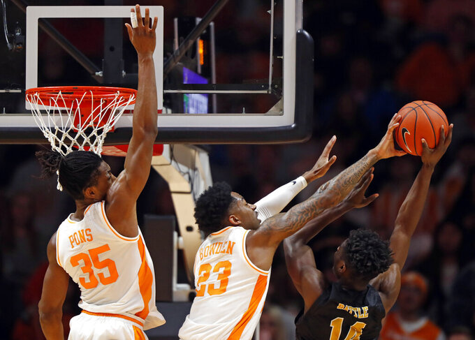 Alabama State forward Brandon Battle (14) has his shot blocked by Tennessee guard Jordan Bowden (23) during the first half of an NCAA college basketball game Wednesday, Nov. 20, 2019, in Knoxville, Tenn. Tennessee guard Yves Pons (35) is behind. (AP Photo/Wade Payne)