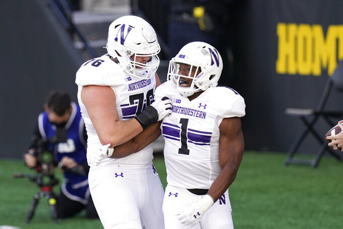 Northwestern running back Jesse Brown (1) celebrates with teammate Ethan Wiederkehr, left, after scoring on a 1-yard touchdown run during the first half of an NCAA college football game against Iowa, Saturday, Oct. 31, 2020, in Iowa City, Iowa. (AP Photo/Charlie Neibergall)
