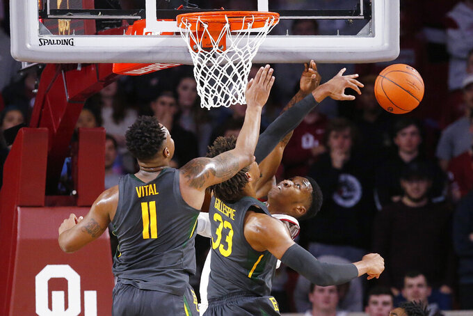 Baylor forward Freddie Gillespie (33) blocks a shot by Oklahoma forward Kristian Doolittle, right, in front of Baylor's Mark Vital (11) during the first half of an NCAA college basketball game in Norman, Okla., Tuesday, Feb. 18, 2020. (AP Photo/Sue Ogrocki)
