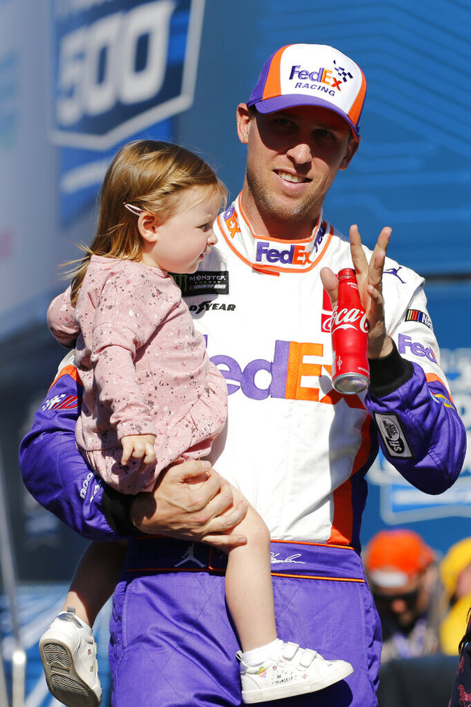 Denny Hamlin carries his daughter, Molly, during introductions for the NASCAR Cup Series race at Martinsville Speedway in Martinsville, Va., Sunday, Oct. 27, 2019. (AP Photo/Steve Helber)