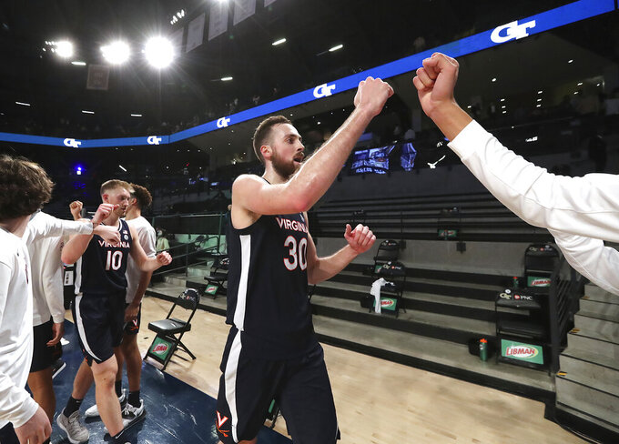 Virginia forwards Sam Hauser, left, and Jay Huff celebrate the team's 57-49 victory over Georgia Tech in an NCAA college basketball game Wednesday, Feb. 10, 2021, in Atlanta. (Curtis Compton/Atlanta Journal-Constitution via AP)