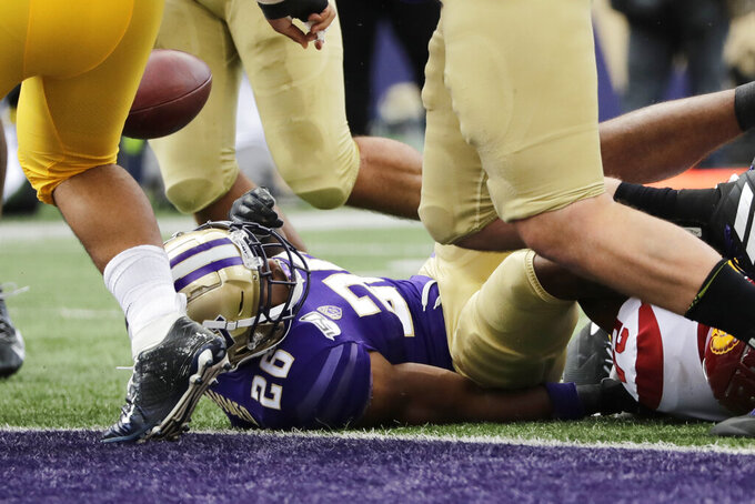 Washington's Salvon Ahmed (26) fumbles the ball just short of the end zone against Southern Cal, but the ball was recovered by Washington for a touchdown in the first half of an NCAA college football game Saturday, Sept. 28, 2019, in Seattle. (AP Photo/Elaine Thompson)