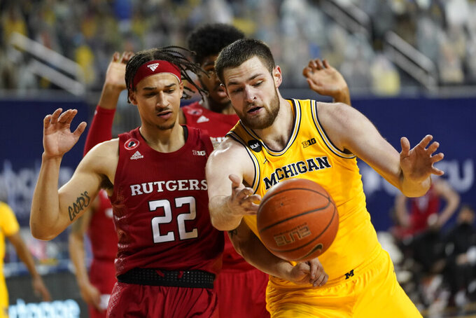 Rutgers guard Caleb McConnell (22) and Michigan Wolverines center Hunter Dickinson (1) battle for a loose ball in the second half of an NCAA college basketball game in Ann Arbor, Mich., Thursday, Feb. 18, 2021. (AP Photo/Paul Sancya)