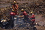 Firefighters looks for victims inside a vehicle days after a dam collapse in Brumadinho, Brazil, Monday, Jan. 28, 2019. Firefighters on Monday carefully moved over treacherous mud, sometimes walking, sometimes crawling, in search of survivors or bodies four days after a dam collapse that buried mine buildings and surrounding neighborhoods with iron ore waste. (AP Photo/Leo Correa)