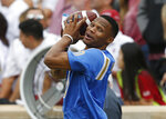 Oklahoma City Thunder guard and UCLA alum Russell Westbrook throws a football around on the sidelines of an NCAA college football game between UCLA and Oklahoma in Norman, Okla., Saturday, Sept. 8, 2018. (AP Photo/Sue Ogrocki)