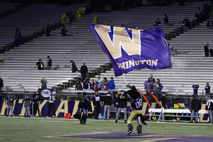 "Harry, the Washington Huskies' mascot, waves a rain-soaked ""W"" flag after an announcement that play would resume following a delay for severe weather during the first quarter of the team's NCAA college football game against California, Saturday, Sept. 7, 2019, in Seattle. (AP Photo/Ted S. Warren)"
