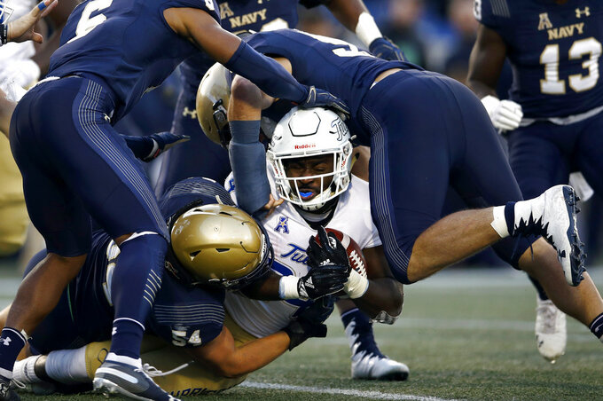 Navy defenders tackle Tulsa running back Corey Taylor II, center, as he rushes the ball in the first half of an NCAA college football game, Saturday, Nov. 17, 2018, in Annapolis, Md. (AP Photo/Patrick Semansky)