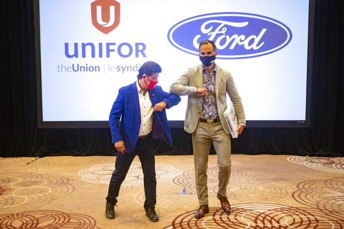 FILE  - In this Aug. 12, 2020 file photo, Unifor President Jerry Dias, left, elbow bumps Ryan Kantautas, Vice President of Human Resources at Ford Canada, after a photo opportunity at the start of formal contract talks with the Detroit Three automakers, Fiat Chrysler, Ford and General Motors, in Toronto. The union that represents Canadian auto workers says it has reached a tentative three-year contract deal with Ford to build five new electric vehicles at a factory near Toronto. Dias says the deal was reached early Tuesday, Sept. 22 after an all-night bargaining session.  (Chris Young/The Canadian Press via AP)
