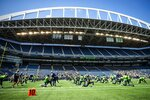 Seattle Seahawks players stretch under the distinctive white rails of Lumen Field before playing a mock game as part of an NFL football training camp at Lumen Field in Seattle, Sunday, Aug. 8, 2021. (Bettina Hansen/The Seattle Times via AP)