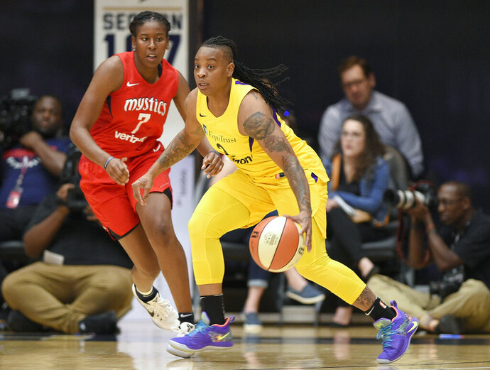 FILE - In this Thursday, Aug. 23, 201 file photo,L os Angeles Sparks guard Riquna Williams, right, dribbles against Washington Mystics guard Ariel Atkins (7) in the first half of a single elimination WNBA basketball playoff game in Washington. The Los Angeles Sparks re-signed free agent Riquna Williams, who was arrested last month after fight with her ex-girlfriend at a Florida home. According to an arrest report, Williams forced her way inside and repeatedly struck Alkeria Davis in the head and pulled her hair. Williams was booked April 29, 2019 for burglary and aggravated assault charges. She pleaded not guilty on May 6 and a hearing is set for June 6. (AP Photo/Nick Wass, File)