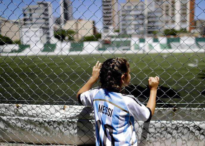 In this Jan. 31, 2019 photo, 12-year-old Candelabra Villegas poses for a photo wearingLionel Messi's national team jersey, in Buenos Aires, Argentina.