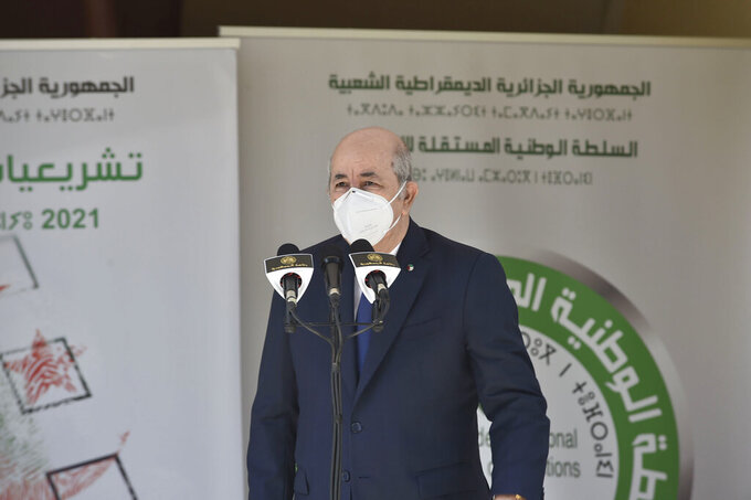 """Algerian president Abdelmadjid Tebboune speaks to the press after casting his vote in the legislative elections at the Ahmed Ouroua school, in Algiers, Algeria, Saturday, June 12, 2021. Algerians vote Saturday for a new parliament in an election with a majority of novice independent candidates running under new rules meant to satisfy demands of pro-democracy protesters and open the way to a """"new Algeria."""" (AP Photo)"""