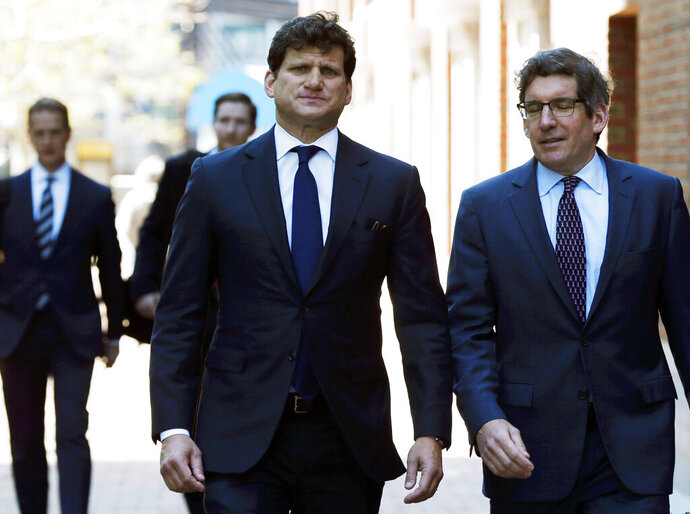 Gordon Caplan, center, arrives at federal court Tuesday, May 21, 2019, in Boston, where he is scheduled to plead guilty to charges in a nationwide college admissions bribery scandal. (AP Photo/Michael Dwyer)