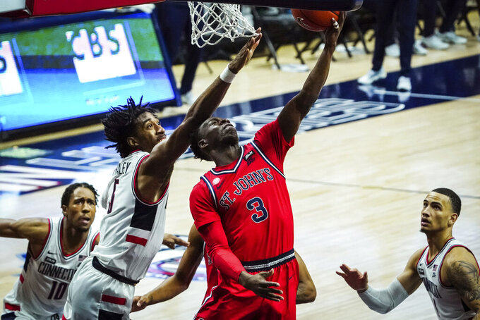 St. John's guard Rasheem Dunn (3) scores against Connecticut forward Isaiah Whaley (5) in the second half of an NCAA college basketball game in Storrs, Conn., Monday, Jan. 18, 2021.  (David Butler II/Pool Photo via AP)