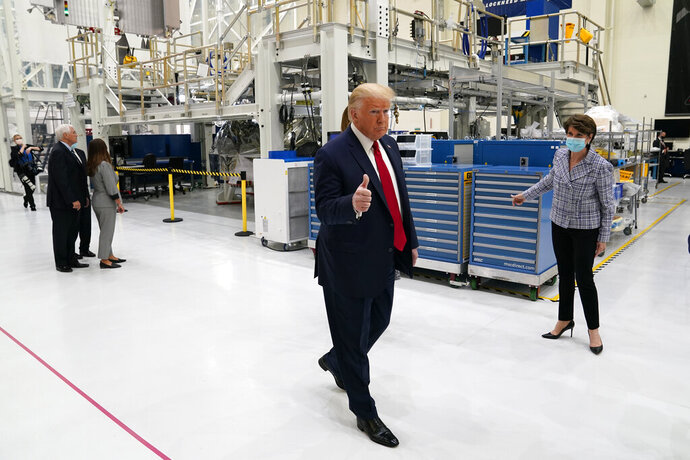 President Donald Trump gestures as he participates in a tour of NASA facilities before viewing the SpaceX Demonstration Mission 2 Launch at Kennedy Space Center, Wednesday, May 27, 2020, in Cape Canaveral, Fla. Marillyn Hewson, chief executive officer of Lockheed Martin, looks on at right. (AP Photo/Evan Vucci)