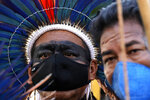Indigenous men react after the Supreme Court judges' decision to suspend the vote that defines the demarcation of Indigenous lands, during a protest in front of the Supreme Court building, in Brasilia, Brazil, Wednesday, Sept. 15, 2021. (AP Photo/Eraldo Peres)