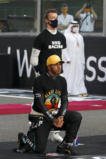 File-This Dec. 13, 2020, file photo shows Mercedes driver Lewis Hamilton of Britain kneeling in support of the Black Lives Matter campaign on the grid before the Formula One at the Yas Marina racetrack in Abu Dhabi, United Arab Emirates. (Hamad Mohammed, Pool via AP, File)