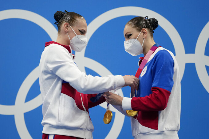First placed Svetlana Kolesnichenko and Svetlana Romashina of Russian Olympic Committee put on their medals during the podium of the duet free routine final at the the 2020 Summer Olympics, Wednesday, Aug. 4, 2021, in Tokyo, Japan. (AP Photo/Alessandra Tarantino)