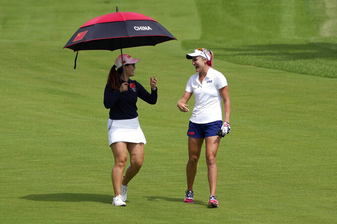 Xiyu Lin, of China, and Lexi Thompson, of the United States, right, laugh during a practice round prior to the women's golf event at the 2020 Summer Olympics, Monday, Aug. 2, 2021, at the Kasumigaseki Country Club in Kawagoe, Japan. (AP Photo/Andy Wong)