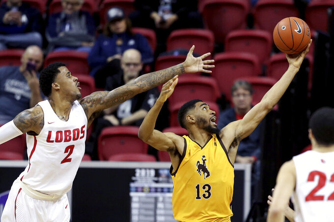 Wyoming's TJ Taylor (13) and New Mexico's Corey Henson (2) reach for a rebound during the first half of an NCAA college basketball game in the Mountain West Conference tournament, Wednesday, March 13, 2019, in Las Vegas. (AP Photo/Isaac Brekken)