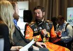 Martin Truex Jr., right, answers questions during an interview during media day for the NASCAR Daytona 500 auto race at Daytona International Speedway, Wednesday, Feb. 14, 2018, in Daytona Beach, Fla. (AP Photo/John Raoux)