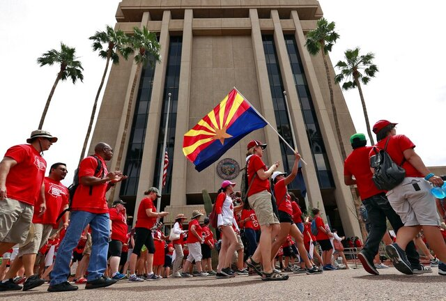 FILE - In this April 30, 2018, file photo, teachers rally outside of Arizona Gov. Doug Ducey's Executive Tower in Phoenix on their third day of walkouts. Public schools in Arizona that have weathered a decade of funding cuts with only partial restoration could see a big infusion of cash if a ballot measure backed by teachers and advocacy groups passes in November, but opponents say Proposition 208 will hurt the economy and only bring partial relief. (AP Photo/Matt York, File)