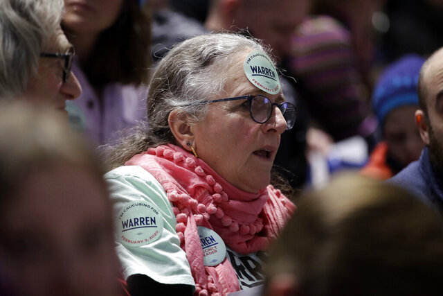 In this Feb. 3, 2020, photo, a woman caucusing for Democratic presidential candidate Sen. Elizabeth Warren, D-Mass., sits in the Warren section at the Precinct 68 caucus at the Knapp Center on the Drake University campus as the night of caucusing gets underway in Des Moines, Iowa. After female candidates helped power the Democratic party to retake the House in 2018 the party's women seem only moderately enthusiastic about voting for a woman for president. AP VoteCast found women in Iowa were only slightly more likely to back a woman than a man. (AP Photo/Gene J. Puskar)