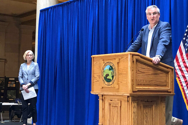 Indiana Gov. Eric Holcomb, right, speaks during a during a news conference while Dr. Kristina Box, the Indiana state health commissioner, listens on Friday, March 27, 2020, at the Statehouse in Indianapolis. Holcomb said the locations of confirmed COVID-19 cases show that all parts of Indiana are seeing illnesses. (AP Photo/Tom Davies)