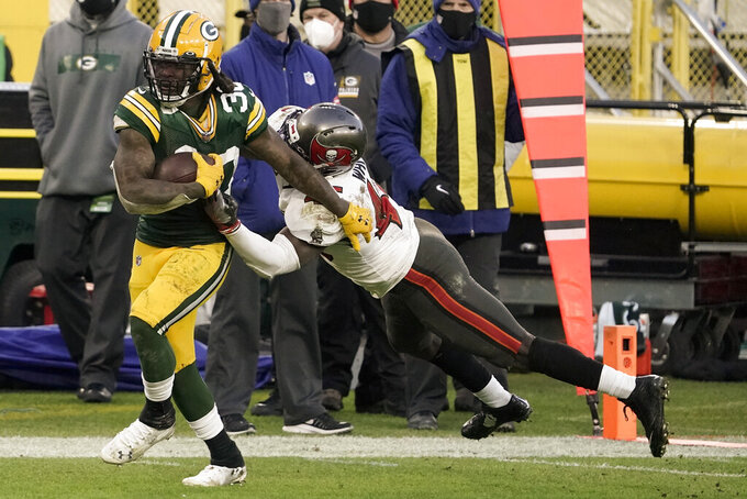 Tampa Bay Buccaneers' Devin White tries to stop Green Bay Packers' Jamaal Williams during the second half of the NFC championship NFL football game in Green Bay, Wis., Sunday, Jan. 24, 2021. (AP Photo/Morry Gash)