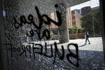 A student walks by windows vandalized by student protesters at the Hong Kong Polytechnic University, Monday, Nov. 11, 2019. A Hong Kong protester was shot by police Monday in a dramatic scene caught on video as demonstrators blocked train lines and roads in a day of spiraling violence fueled by demands for democratic reforms. (AP Photo/Dita Alangkara)