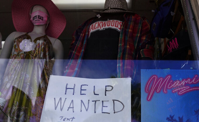 """FILE - In this Jan. 7, 2021 file photo, a """"Help Wanted,"""" sign is shown in the window of a souvenir shop in Miami Beach, Fla.  Hiring has weakened for six straight months. Nearly 10 million jobs remain lost since the coronavirus struck. And this week, the Congressional Budget Office forecast that employment won't regain its pre-pandemic level until 2024.  (AP Photo/Wilfredo Lee)"""