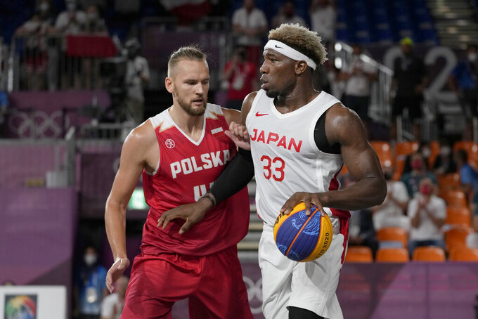 Japan's Ira Brown (33) dribbles as Poland's Szymon Rduch (44) defends during a men's 3-on-3 basketball game at the 2020 Summer Olympics, Saturday, July 24, 2021, in Tokyo, Japan. (AP Photo/Jeff Roberson)