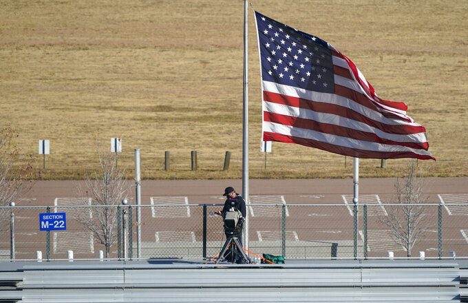 High winds unfurl a United States flag as it stands over the lone videographer allowed in the east stands of an NCAA college football game between Boise State and Air Force, Saturday Oct. 31, 2020, at Air Force Academy, Colo. (AP Photo/David Zalubowski)
