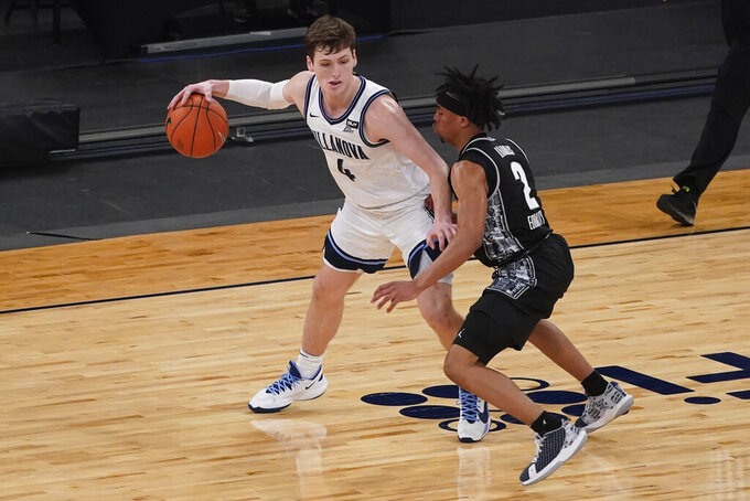 Villanova guard Chris Arcidiacono (4) drives against Georgetown guard Dante Harris (2) during the first half of an NCAA college basketball game in the quarterfinals of the Big East conference tournament, Thursday, March 11, 2021, in New York. (AP Photo/Mary Altaffer)