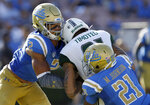 FILE - In this Sept. 9, 2017, file photo, Hawaii wide receiver Kalakaua Timoteo, center, drops the ball as he gets hit by UCLA linebacker Josh Woods, left, and defensive back Mossi Johnson (21) at the goal line, during the second half of an NCAA college football game in Pasadena, Calif. Woods was penalized for targeting and ejected. The NCAA football rules committee has proposed giving replay officials more leeway to overturn targeting fouls. The rules committee met in Indianapolis this week and announced on Friday, March 1, 2019, its proposed changes. The proposals must be approved by the football oversight committee in April. They would go into effect next season.(AP Photo/Alex Gallardo, File)