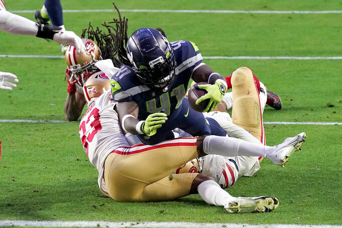 Seattle Seahawks running back Alex Collins scores a touchdown as San Francisco 49ers defensive back Tarvarius Moore (33) defends during the second half of an NFL football game, Sunday, Jan. 3, 2021, in Glendale, Ariz. (AP Photo/Ross D. Franklin)