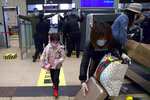 Passengers wearing face masks to protect against the spread of new coronavirus pass through security checks at Hankou train station after of the resumption of train services in Wuhan in central China's Hubei Province, Wednesday, April 8, 2020. After 11 weeks of lockdown, the first train departed Wednesday morning from a re-opened Wuhan, the origin point for the coronavirus pandemic, as residents once again were allowed to travel in and out of the sprawling central Chinese city. (AP Photo/Ng Han Guan)