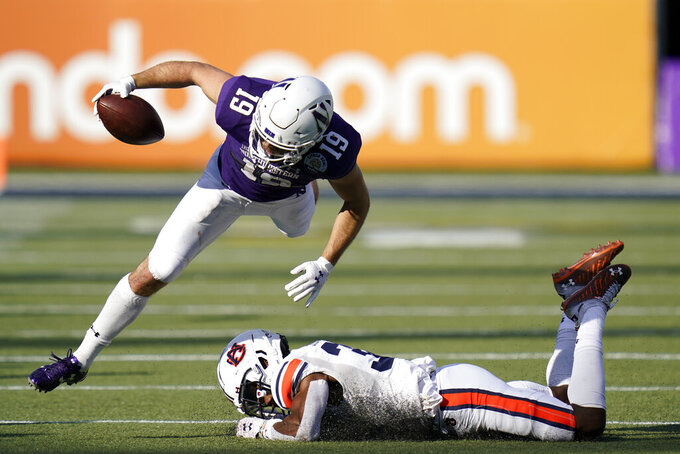 Northwestern wide receiver Riley Lees (19) tries to leap over Auburn defensive back Jaylin Simpson, lower right, after a short gain during the second half of the Citrus Bowl NCAA college football game, Friday, Jan. 1, 2021, in Orlando, Fla. Northwestern defeated Auburn 35-19. (AP Photo/John Raoux)