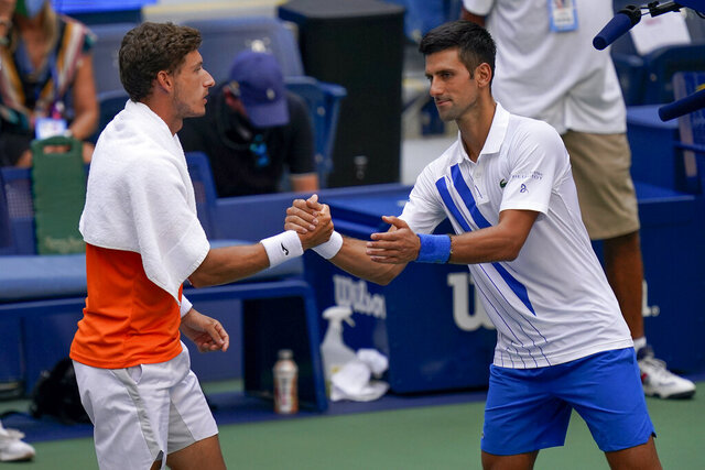 Novak Djokovic, of Serbia, shakes hands with Pablo Carreno Busta, of Spain, after defaulting the match during the fourth round of the US Open tennis championships, Sunday, Sept. 6, 2020, in New York. Djokovic inadvertently hit a line judge with a ball after hitting the ball in reaction to losing a point to Carreno Busta. (AP Photo/Seth Wenig)