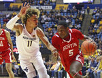 West Virginia forward Emmitt Matthews Jr. (11) defends against Boston University guard Walter Whyte (5) during the first half of an NCAA college basketball game Friday, Nov. 22, 2019, in Morgantown, W.Va. (AP Photo/Kathleen Batten)