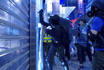 A protester damages a glass window on the streets of Hong Kong on Friday, Oct. 4, 2019. Masked protesters streamed into Hong Kong streets Friday after the city's embattled leader invoked rarely used emergency powers to ban masks at rallies in a hardening of the government's stance after four months of anti-government demonstrations. (AP Photo/Vincent Yu)