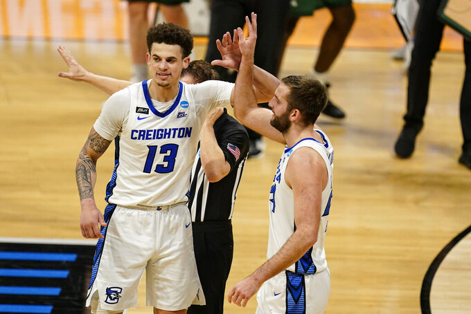 Creighton forward Christian Bishop (13) and guard Mitch Ballock (24) celebrate in the second half of a second round game in the NCAA men's college basketball tournament at Hinkle Fieldhouse in Indianapolis, Monday, March 22, 2021. (AP Photo/Michael Conroy)