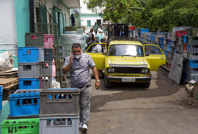 Customers enter through the back of Mercabal wholesale market, to load their merchandise in Havana, Cuba, Thursday, July 30, 2020. The government is letting private businesses buy wholesale for the first time. (AP Photo/Ismael Francisco)