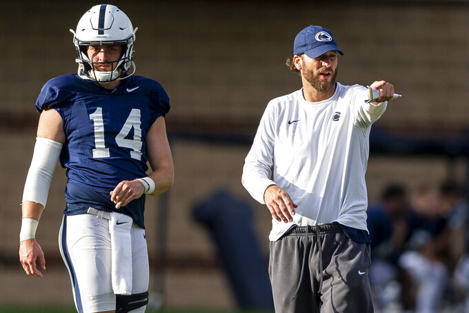 Penn State quarterback Sean Clifford stands next to offensive coordinator Mike Yurcich during NCAA college football practice Wednesday, Oct. 6, 2021, in State College, Pa. (Joe Hermitt/The Patriot-News via AP)