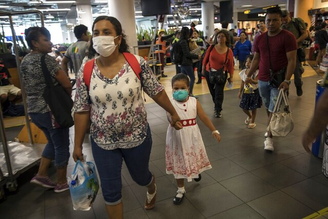 Wearing masks, passenger Gladys Ruiz Torres walks with her daughter Natali Oliva to the departure lounge at the international airport in Lima, Peru, Friday, March 6, 2020. Peruvian President Martin Vizcarra announced the first case of the new coronavirus in the country. (AP Photo/Rodrigo Abd)