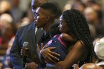 FILE - In this June 18, 2019 file photo Dravon Ames, holding microphone, speaks to Phoenix Police Chief Jeri Williams and Phoenix Mayor Kate Gallego, as his fiancee, Iesha Harper, right, holds 1-year-old daughter London, at a community meeting in Phoenix. Still stinging from national outrage sparked this summer by a videotaped encounter of officers pointing guns and cursing at the family, community members are holding low-key meetings aimed at helping Phoenix officials figure out how citizens could help oversee the city's officers. (AP Photo/Ross D. Franklin, File)