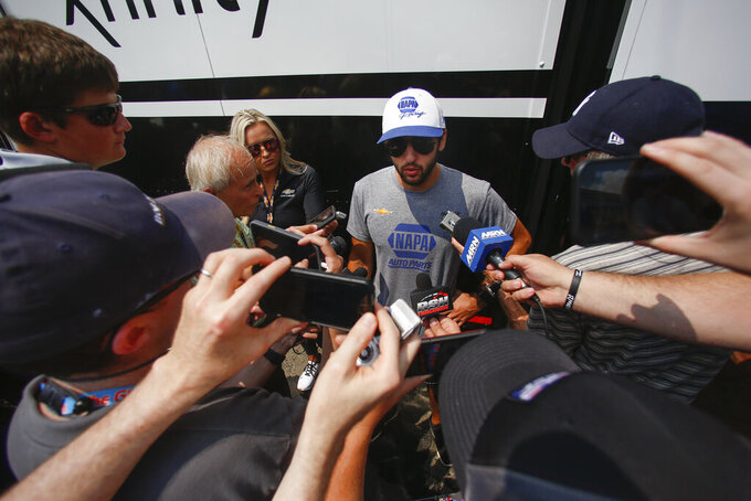 Chase Elliott, center, answers questions during a media availability session before a NASCAR Cup Series auto race in Watkins Glen, N.Y., Sunday, Aug. 8, 2021. (AP Photo/Joshua Bessex)