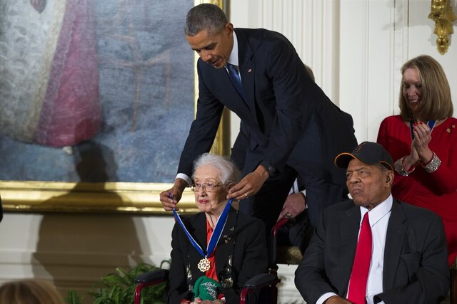 FILE - In this Nov. 24, 2015 photo, Willie Mays, right, looks on as President Barack Obama presents the Presidential Medal of Freedom to NASA mathematician Katherine Johnson during a ceremony in the East Room of the White House, in Washington. Johnson, a mathematician on early space missions who was portrayed in film