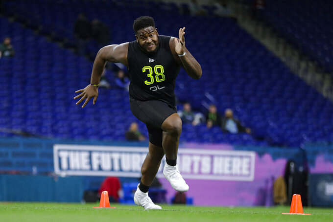 FILE - In this Feb. 28, 2020, file photo, Mississippi State offensive lineman Tyre Phillips runs a drill at the NFL football scouting combine in Indianapolis. In their quest to keep quarterback Lamar Jackson upright and running, the Baltimore Ravens have put a priority on fortifying their offensive line following the retirement of eight-time Pro Bowl guard Marshal Yanda. The Baltimore Ravens selected Phillips in the third round of the 2020 NFL Draft. (AP Photo/Michael Conroy, File)